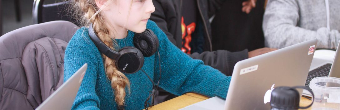 Young girl sitting at a desk with laptop and headphones learning STEAM