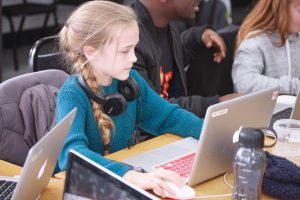 Young girl sitting at a desk with laptop and headphones learning Girls STEAM